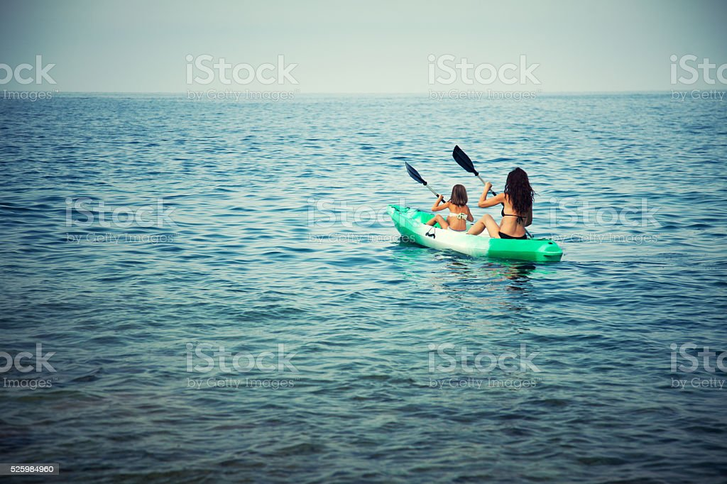 Woman and little girl in kayak on the sea stock photo