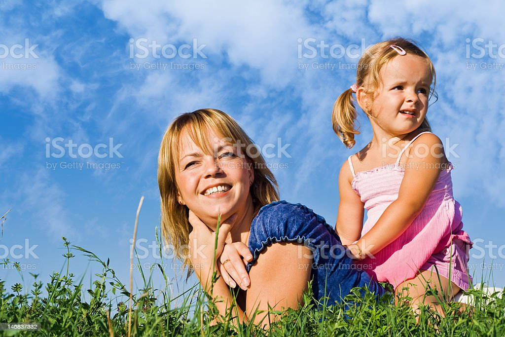 Woman and little girl in the grass royalty-free stock photo
