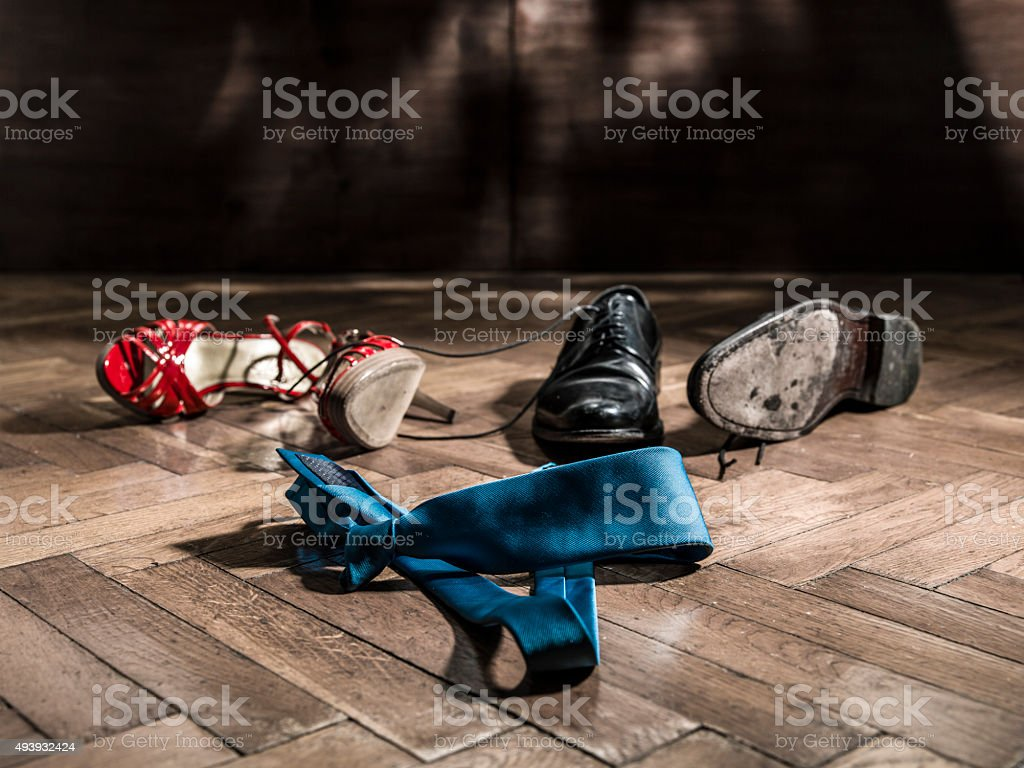 woman and male shoes dropped on the floor stock photo