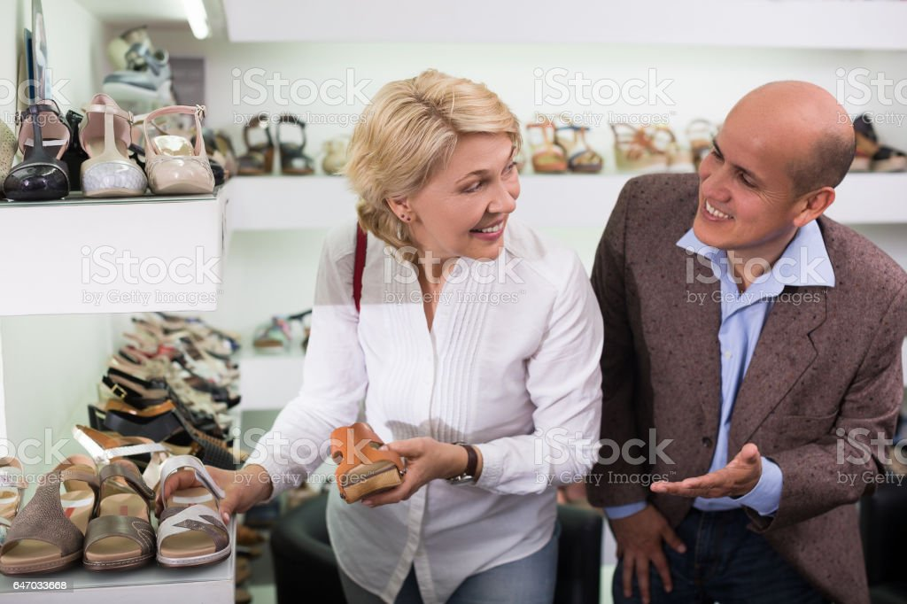 Woman and man buying sandals stock photo