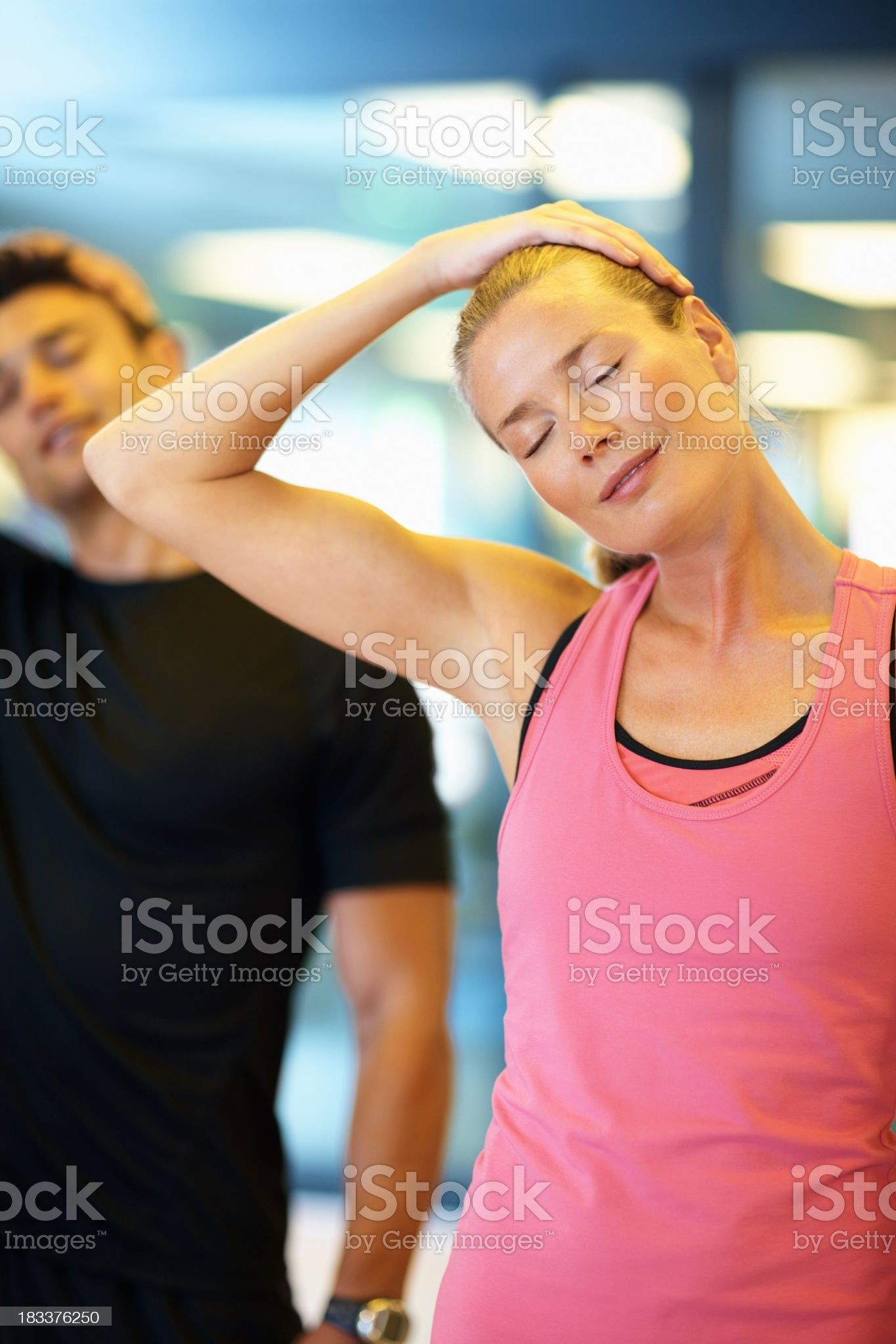 Woman and man flexing their necks at the gym royalty-free stock photo