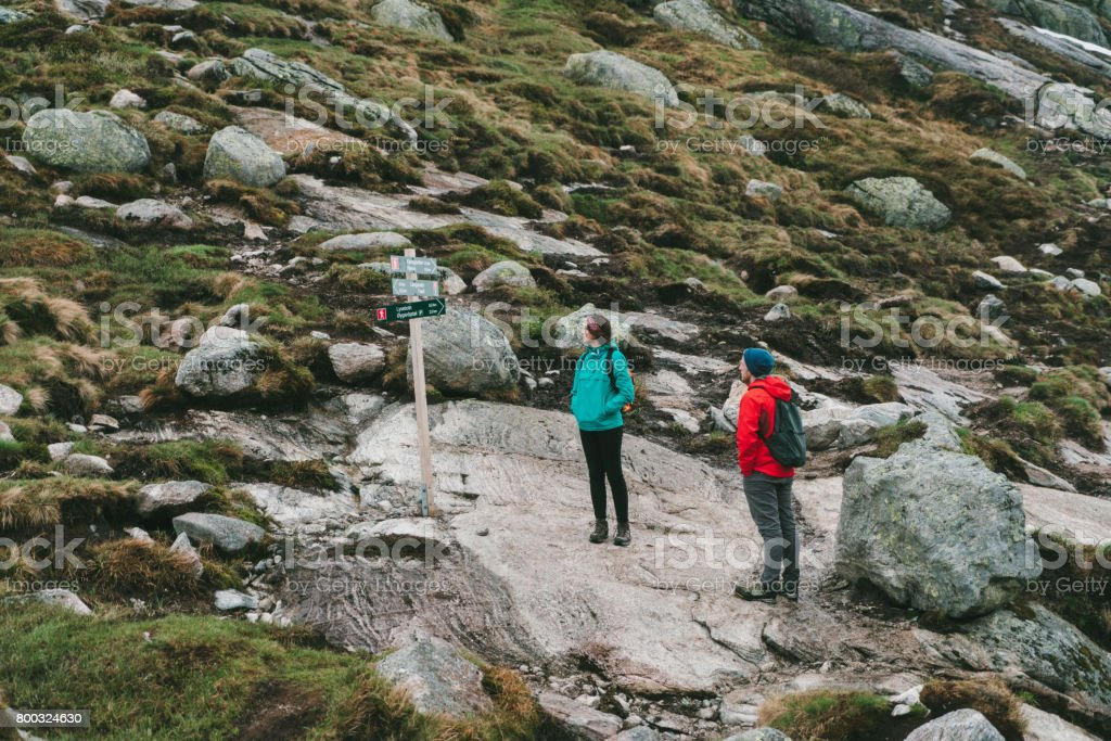 Woman and man hiking in mountains in Norway stock photo