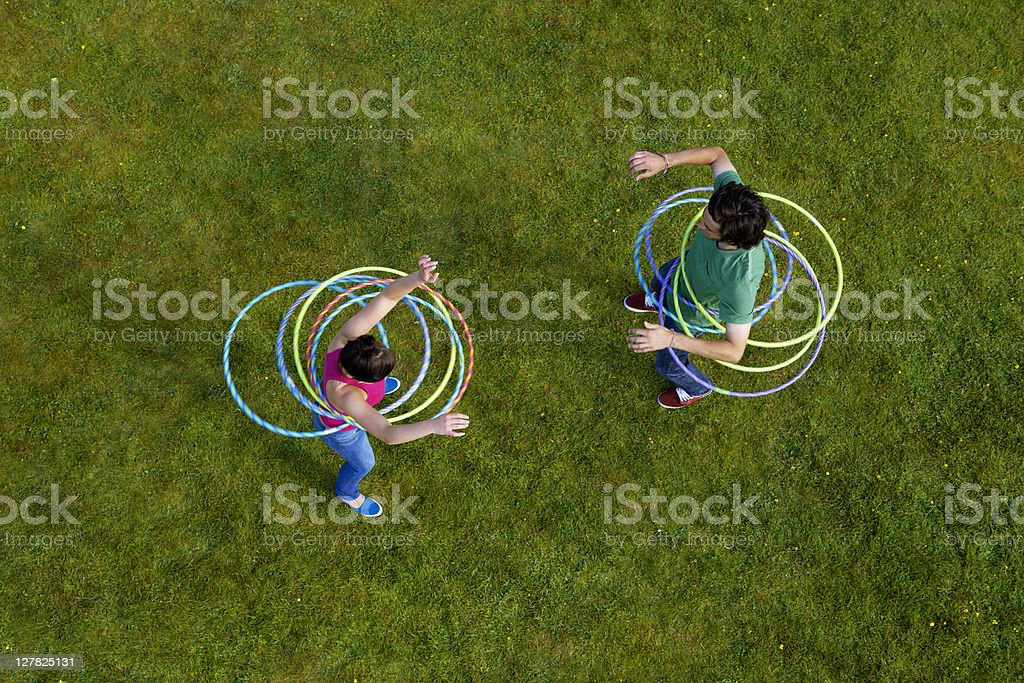 Woman and man hula hooping in grass stock photo