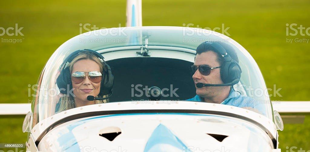 Woman and man pilot looking at camera, preparing for flying stock photo