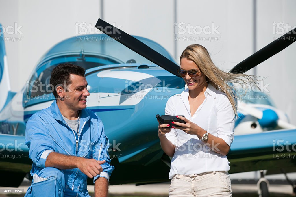 Woman and man pilot looking at map, preparing for flying stock photo