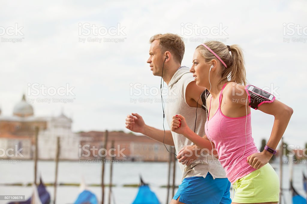 Woman and man running outdoors together stock photo