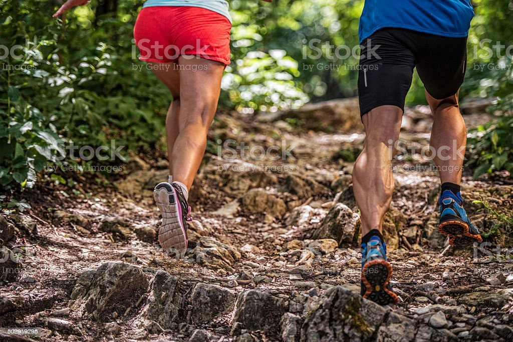 Woman and man running up a rocky forest path stock photo