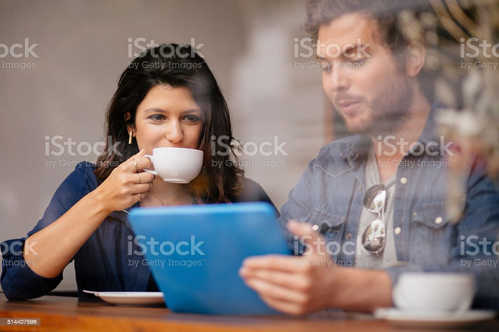 Woman and Man sitting in coffee shop with Tablet stock photo