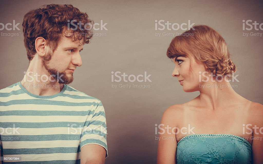 woman and man sitting on sofa looking to each other. stock photo