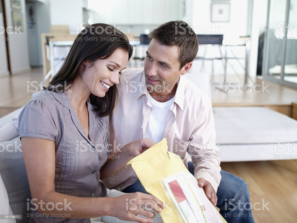 Woman and man sitting on sofa with package smiling stock photo