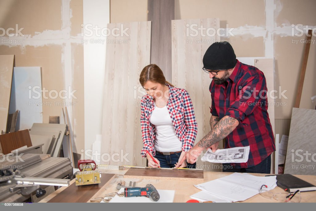 Woman using power tools in a carpenter workshop, man teaching her how...