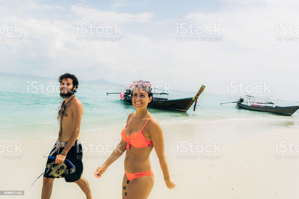 Woman and man walking on the beach stock photo