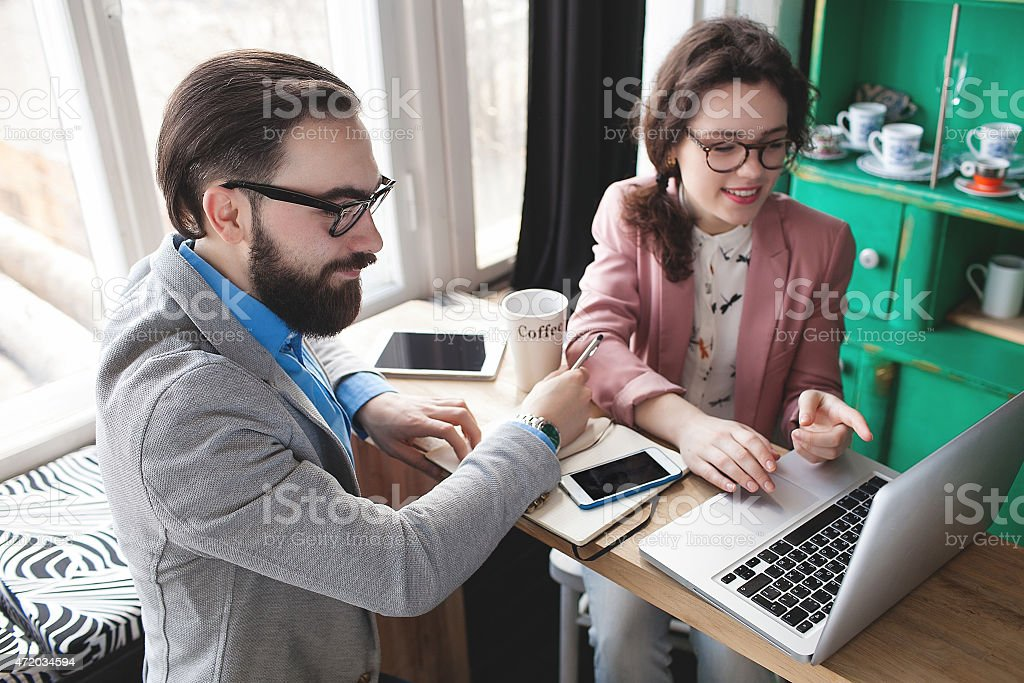 Woman and man work on laptop in cafe with phone and tablet stock photo