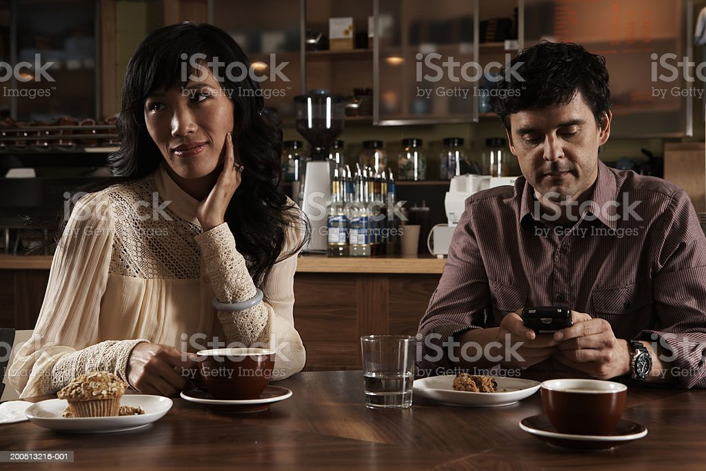 Woman and mature man sitting at table in cafe, man using palmtop royalty-free stock photo