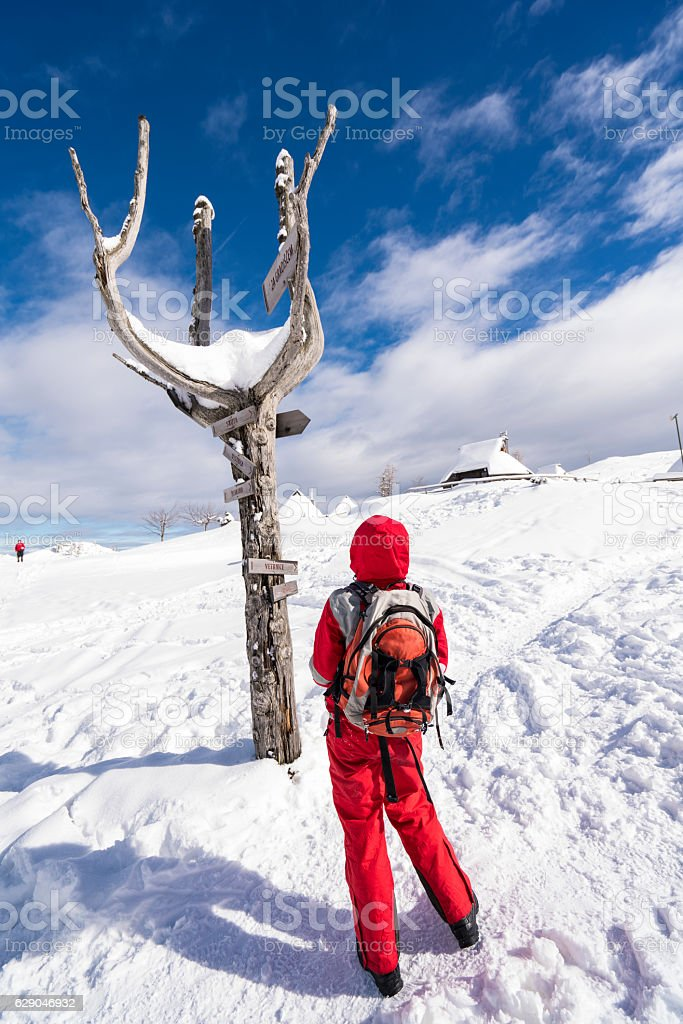 Woman and mountain signposts at Plateau Velika Planina, Slovenia stock photo
