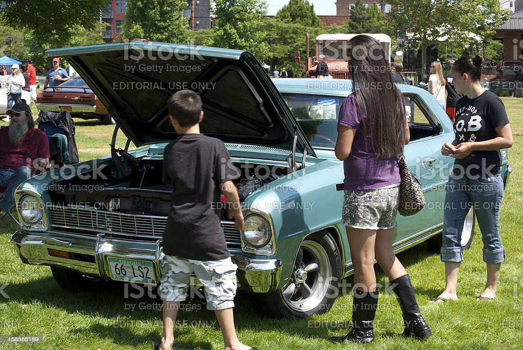 Woman and others looking at car on display stock photo