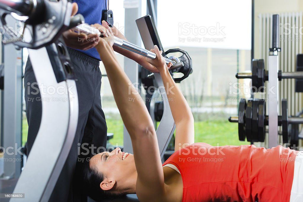 woman and Personal Trainer in gym, with dumbbells royalty-free stock photo