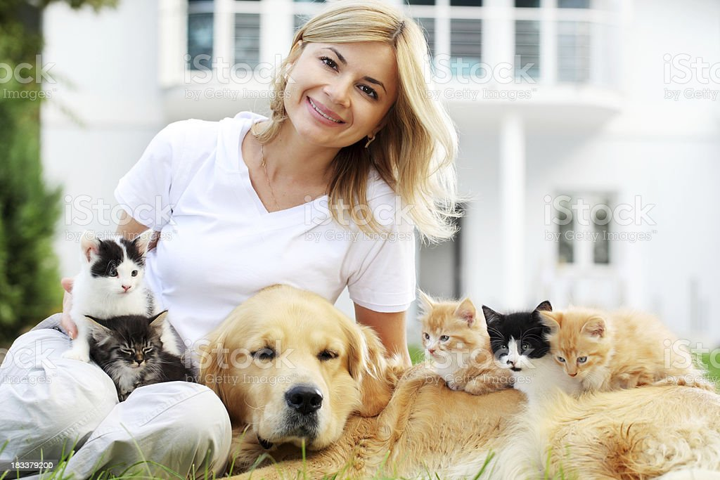 Woman and pets resting on the green garden. royalty-free stock photo