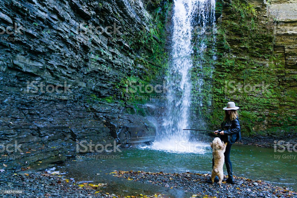 Woman and Puppy Play Fetch in Waterfall stock photo