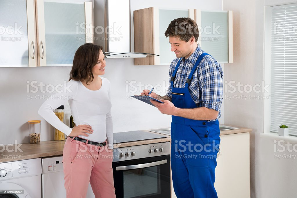 Woman And Repairman In Kitchen stock photo