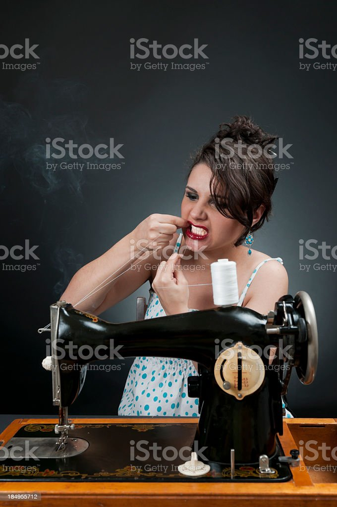 Woman and sewing machine, cutting the thread with her teeth stock photo
