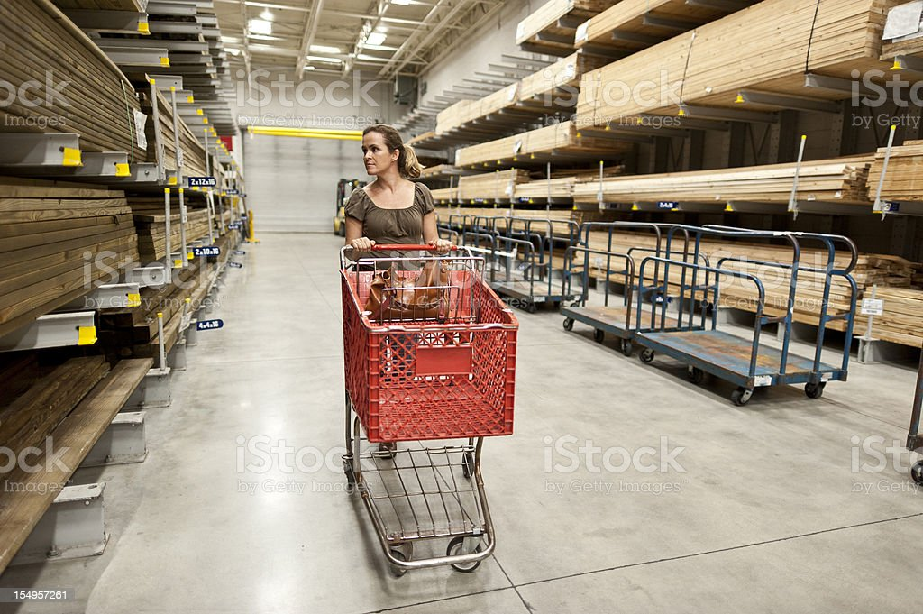 woman and shopping cart in lumber aisle stock photo