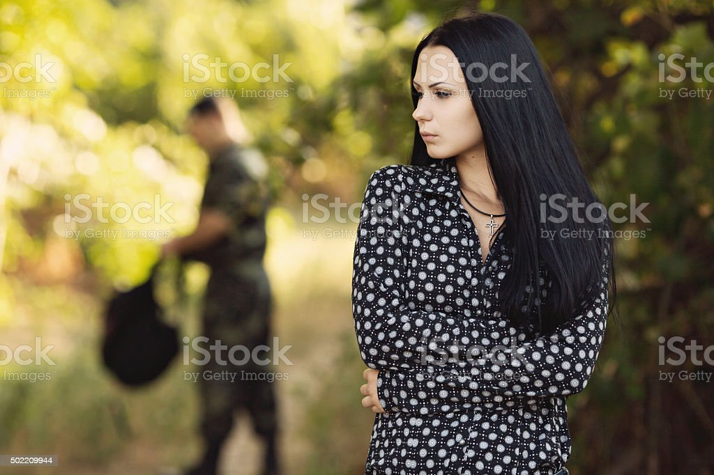 Woman and soldier in a military uniform stock photo