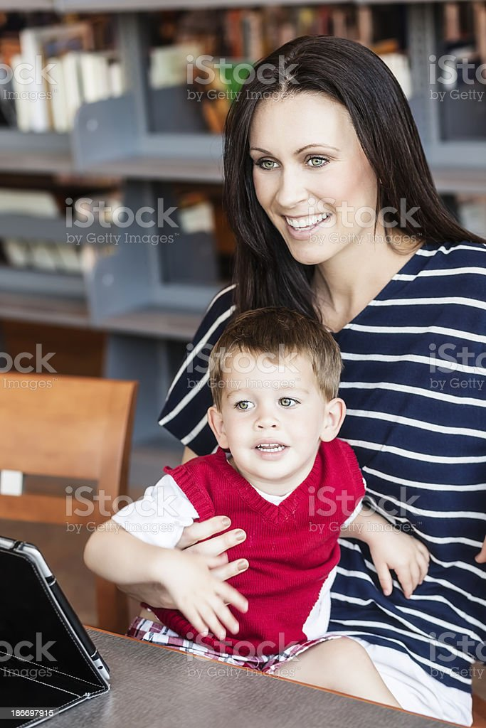 Woman and Son With Tablet Computer in Library royalty-free stock photo