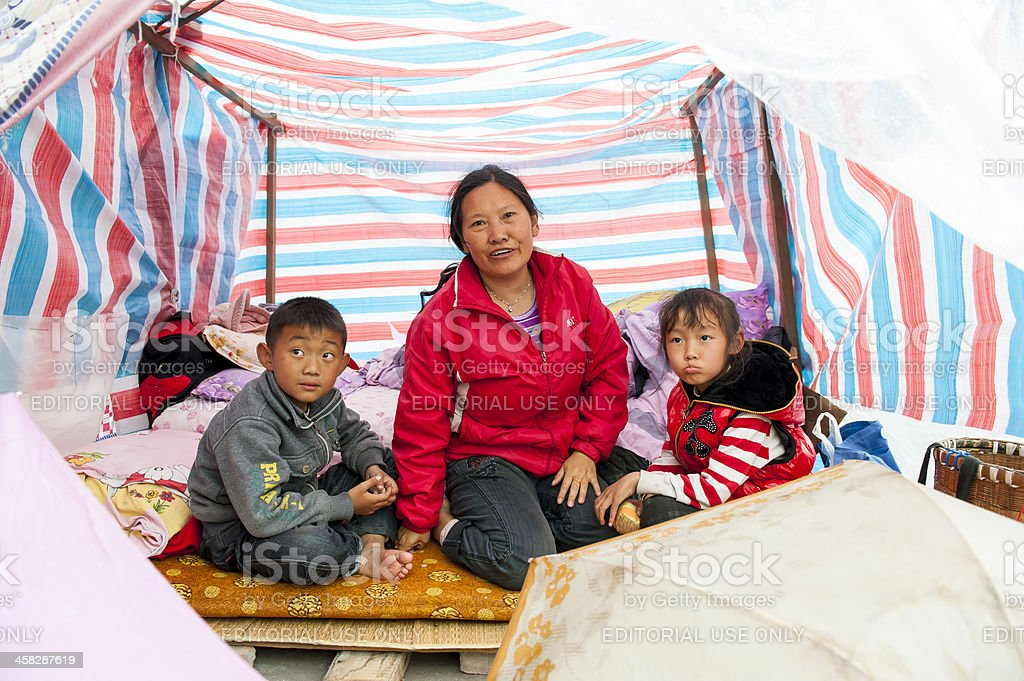 Woman and two kids sitting in temp tent, Yaan, China royalty-free stock photo