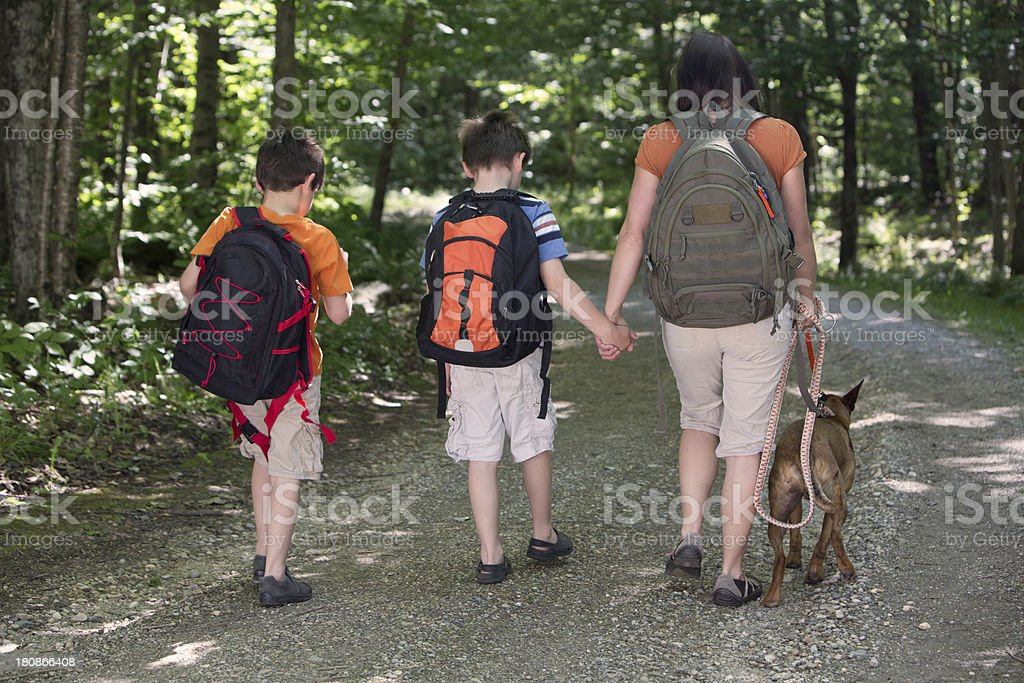 Woman and two young boys hiking with a brown dog royalty-free stock photo
