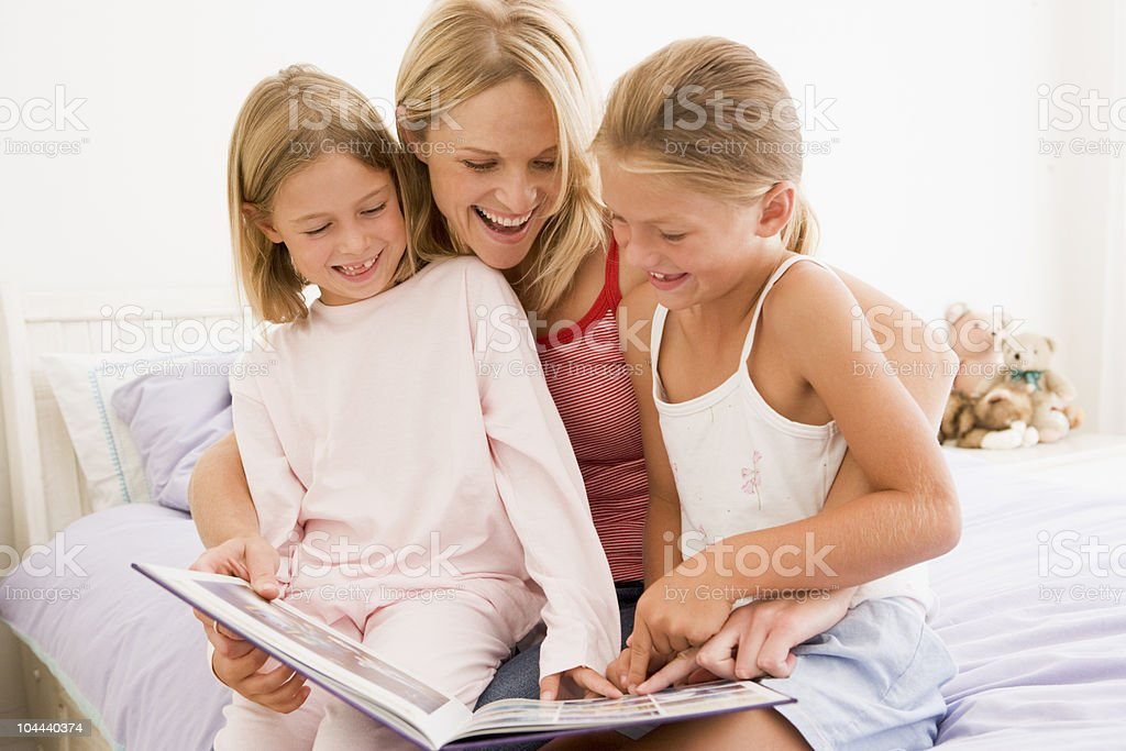 Woman and two young girls in bedroom reading book stock photo