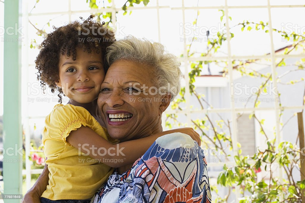 Woman and young girl embracing outdoors stock photo