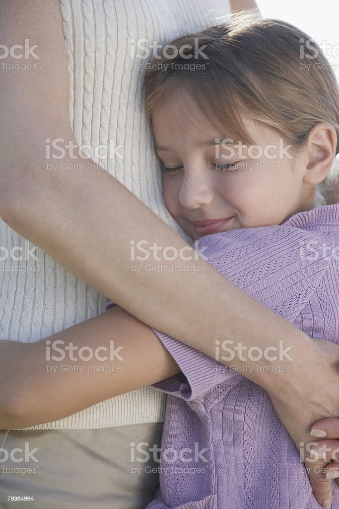 Woman and young girl hugging outdoors royalty-free stock photo