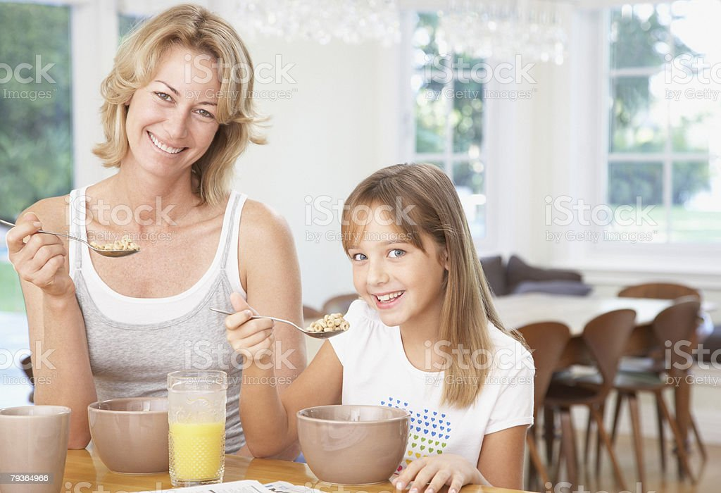 Woman and young girl in kitchen eating breakfast royalty-free stock photo