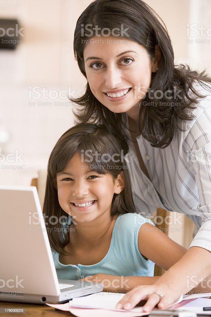 Woman and young girl in kitchen with laptop smiling royalty-free stock photo