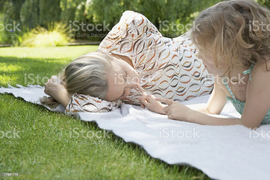 Woman and young girl lying down on blanket outdoors royalty-free stock photo