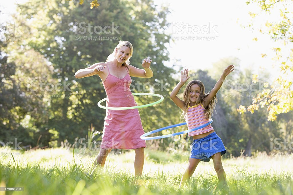 Woman and young girl outdoors using hula hoops, smiling stock photo