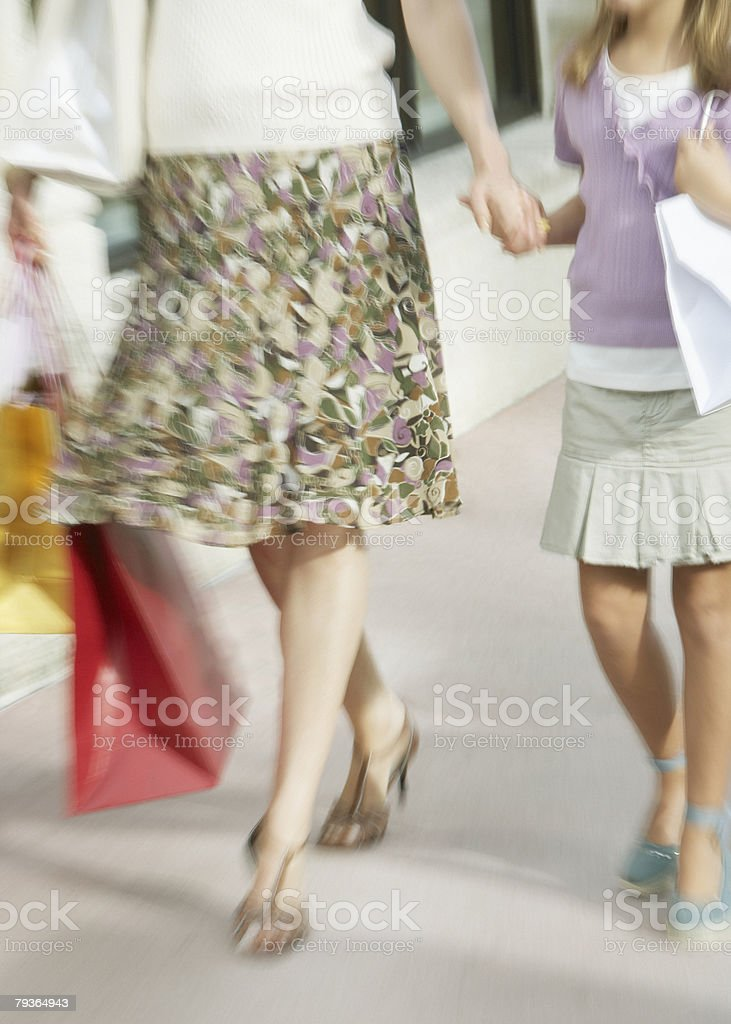 Woman and young girl outdoors with shopping bags royalty-free stock photo