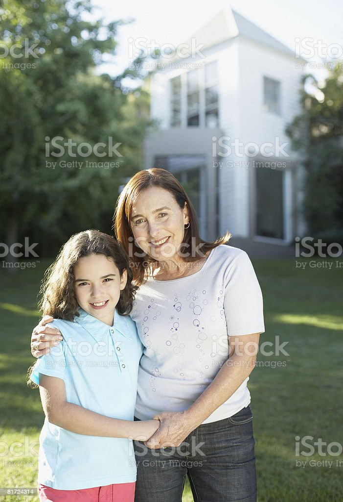 Woman and young girl standing outdoors holding hands and smiling royalty-free stock photo