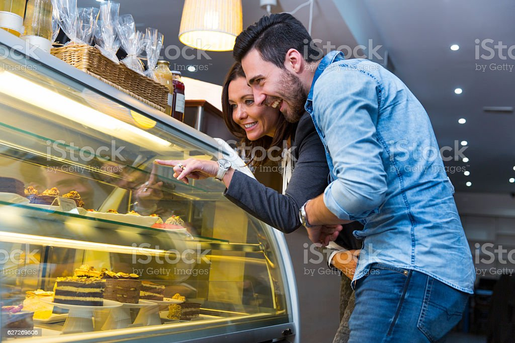 Woman and young man looking at display window with cakes stock photo