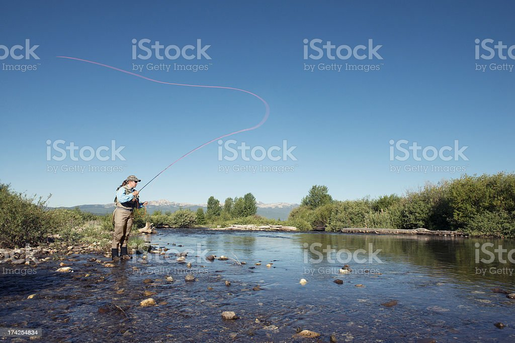 Woman Angler Fishing Outdoors in Blue Montana River stock photo