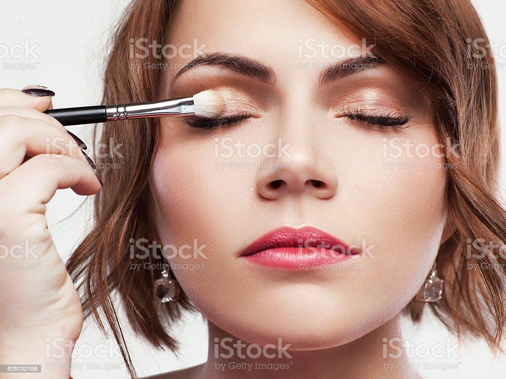Woman applies eyeshadow. Nude eye makeup stock photo
