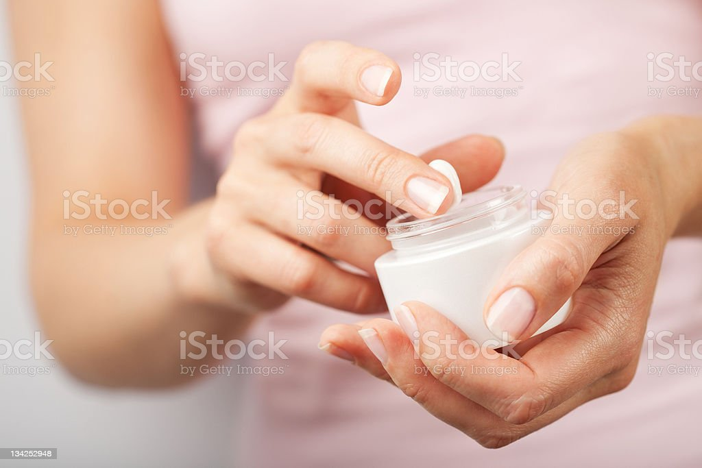 A woman applying a white cream from a bottle stock photo