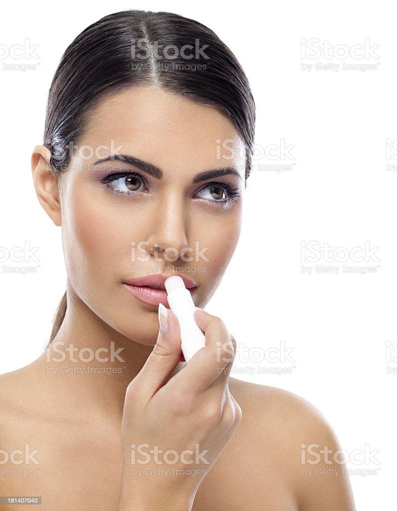 Woman applying balsam on lips stock photo