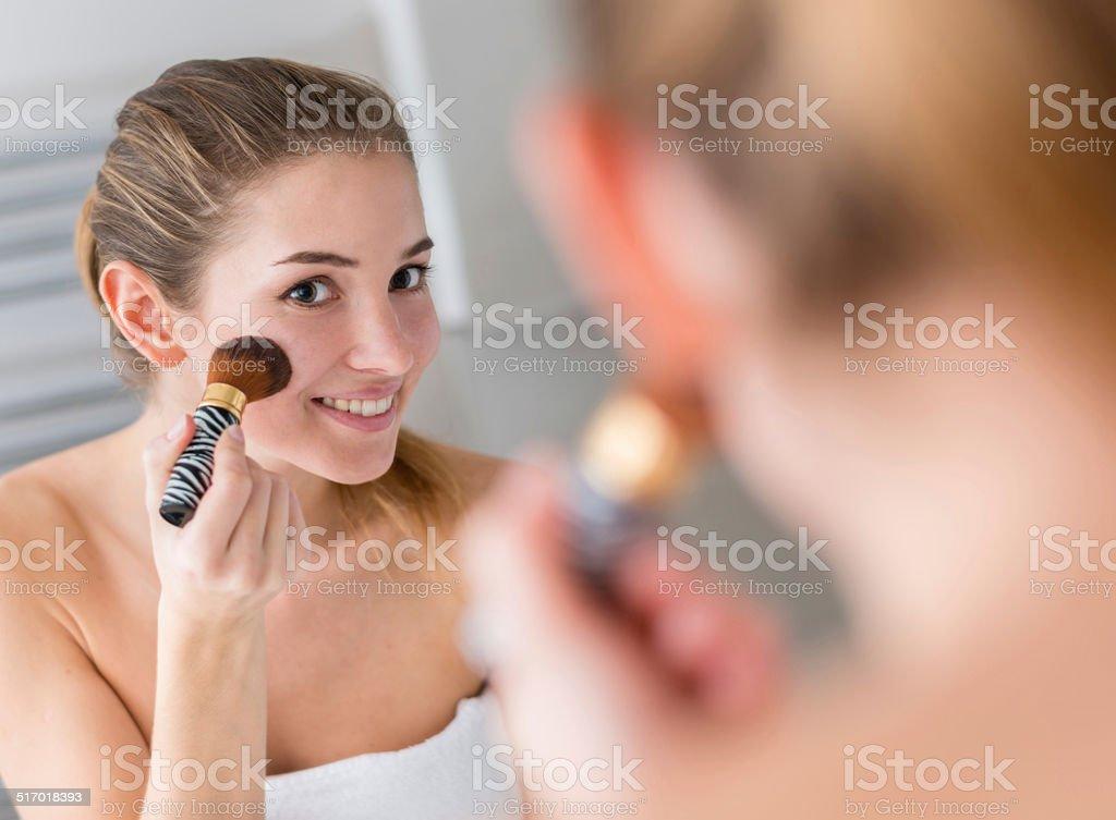 Woman applying blusher stock photo