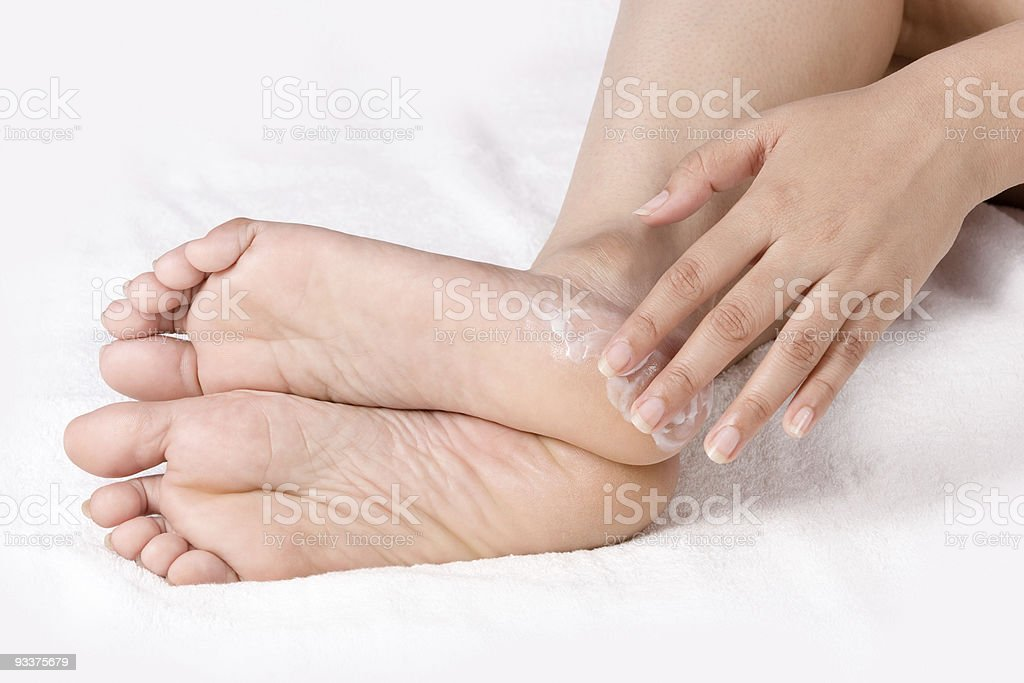 Woman applying body cream to feet on bed  stock photo