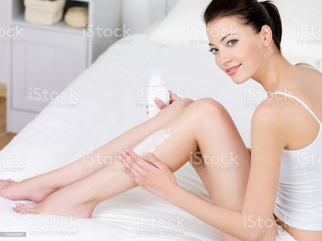 Woman applying body lotion on her legs royalty-free stock photo