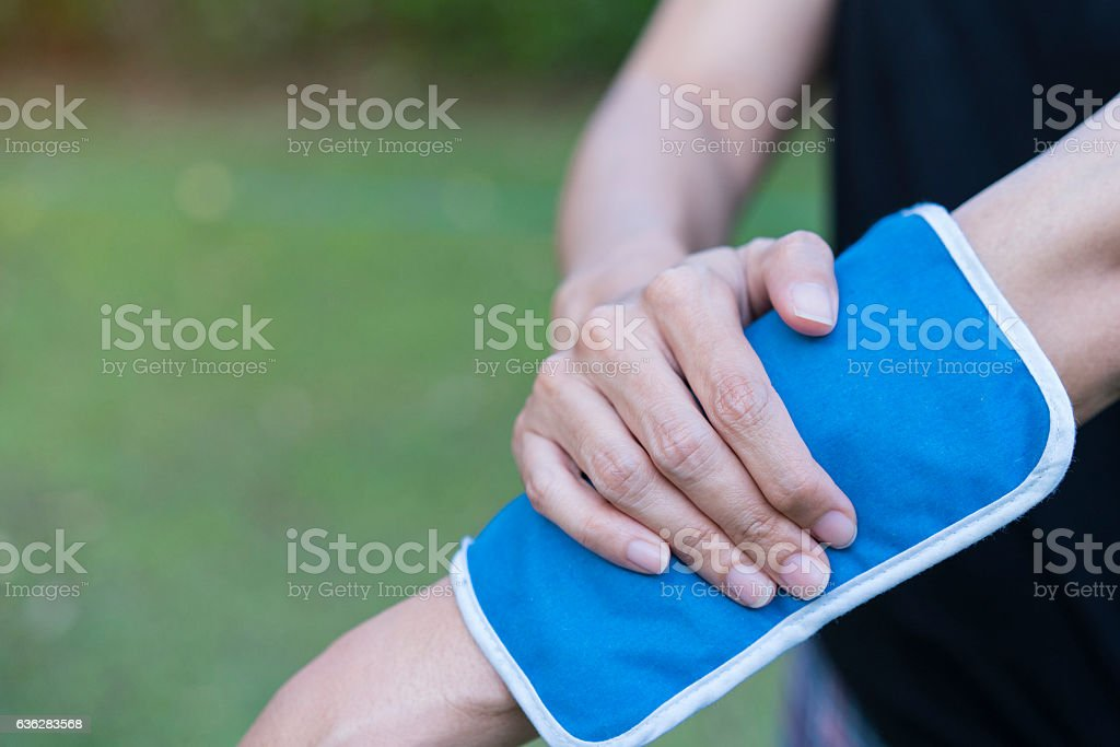 woman applying cold pack on her arm stock photo