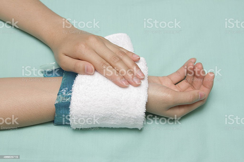 woman applying cold pack on  swollen hurting wrist stock photo