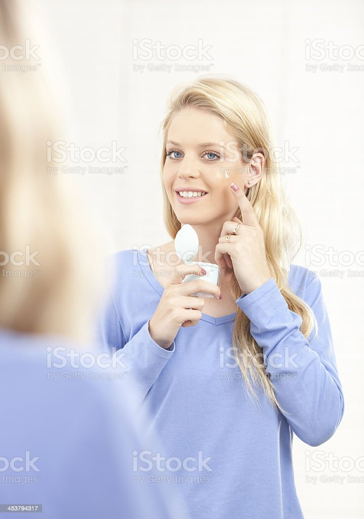 Woman applying cosmetic cream on face. royalty-free stock photo